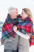 Couple wrapped up in blanket on the beach — Stock fotografie