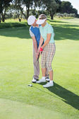 Man coaching his partner on the putting green — Stock Photo