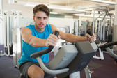 Focused man on the exercise bike — Stock Photo