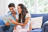 Couple reading book on the sofa — Stock Photo