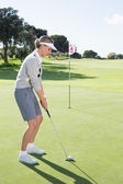 Lady golfer on the putting green — Stockfoto