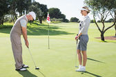 Golfing couple on putting green at eighteenth hole — Stok fotoğraf