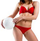 Fit girl in bikini holding football — Stock Photo