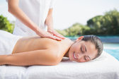 Happy brunette getting a massage poolside — Stock Photo