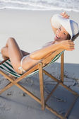 Woman relaxing in deck chair on the beach — Foto Stock