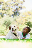 Boy lying with labrador dog — Stockfoto
