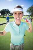 Golfer smiling with partner cheering behind — Stock fotografie