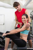 Trainer helping his client on rowing machine — 图库照片