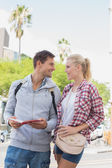 Tourist couple consulting the guide book — Stockfoto