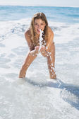 Woman in bikini splashing on the beach — Stock Photo