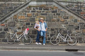 Hip couple standing by wall with bikes — Foto Stock