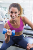 Pretty fit woman lifting blue dumbbell smiling at camera — Stock Photo