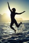 Blonde in sea leaping in bikini — Stock Photo