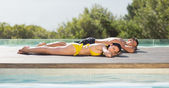 Couple lying poolside on holidays — Stok fotoğraf