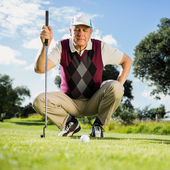 Golfer kneeling watching gold ball — Stock Photo