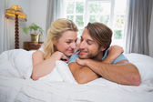 Couple relaxing on bed — Stockfoto