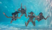 Friends underwater in swimming pool — Stock Photo