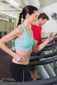 Couple running together on treadmills — Stock Photo