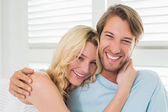 Couple sitting on couch laughing — Stockfoto