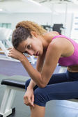 Tired fit woman taking a break on the bench — Stock Photo