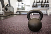 Black kettlebell on the weights room floor — Stock Photo