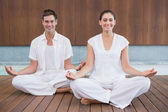 Couple in white sitting in lotus pose — Stock Photo