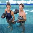 Man and woman with dumbbells in the pool — Stock Photo #48330255