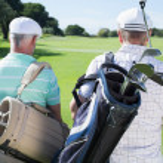 Golfer friends walking holding golf bags — Stock Photo