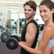 Couple lifting dumbbells together — Stock Photo
