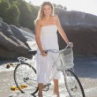 Blonde standing with bike on beach — Stock Photo #48332571