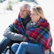 Couple wrapped up in blanket on the beach — Stock Photo #48332943