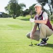 Golfer kneeling holding his golf club — Stock Photo #48334185
