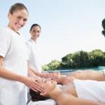 Masseuses massaging couple — Stock Photo