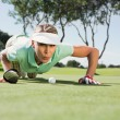 Golfer blowing her ball on putting green — Stock Photo #48335149
