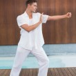 Handsome man in white doing tai chi — Stock Photo #48335283