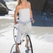 Blonde standing with bike on beach — Stock Photo #48335505