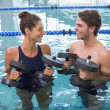 Man and woman with dumbbells in the pool — Stock Photo #48335641
