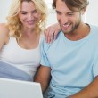 Couple on couch using laptop — Stock Photo