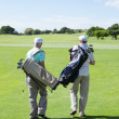 Golfer friends holding their golf bags — Stock Photo