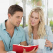Hip couple having coffee and reading book — Stock Photo #48336331