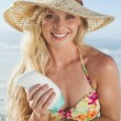 Blonde applying suncream — Stock Photo #48336421
