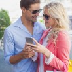 Stylish couple looking at smartphone — Stock Photo