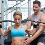 Female bodybuilder using weight machine — Stock Photo #48336489