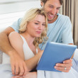 Couple on couch using tablet — Stock Photo #48336785