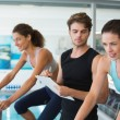 Fit women in a spin class with trainer taking notes — Stock Photo #48336815