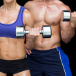 Bodybuilding couple posing with large dumbells — Стоковое фото