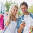 Couple looking at smartphone on shopping trip — Fotografia Stock  #48338679