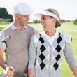 Golfing couple smiling on the putting green — Stock Photo #48339643