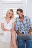 Couple sitting on floor using laptop — Stock Photo