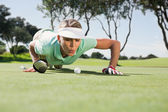 Golfer blowing her ball on putting green — Stok fotoğraf